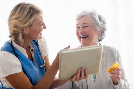 sheltered accommodation: Nurse showing a tablet to a senior woman in a retirement home