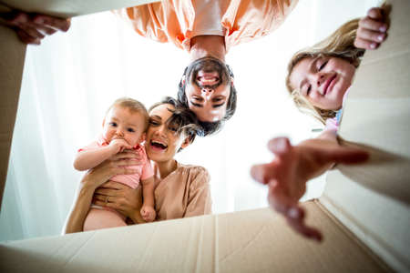 directly below: Directly below shot of happy family seen from cardboard box LANG_EVOIMAGES