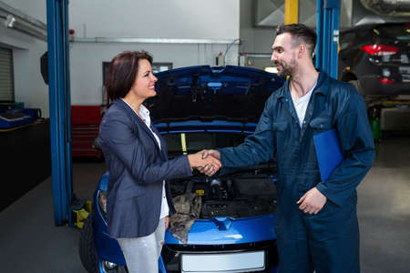 satisfied customer: Satisfied customer shaking hands with mechanic at the repair garage