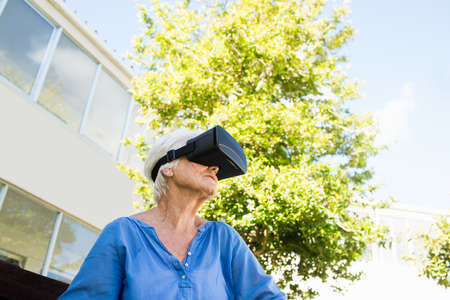 sheltered accommodation: Senior woman looking in 3D glasses in a retirement home