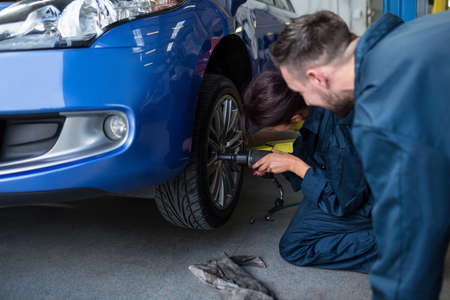 pneumatic: Mechanics fixing a car wheel with pneumatic wrench at the repair garage LANG_EVOIMAGES