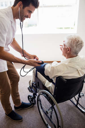 sheltered accommodation: Nurse measuring the blood pressure of a senior man in a retirement home
