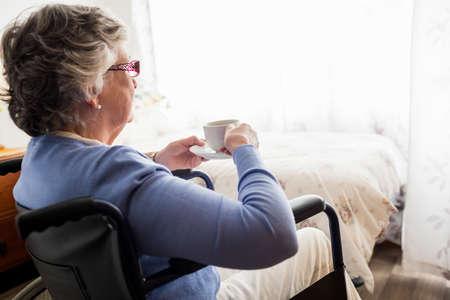 paraplegico: Senior woman drinking coffee in a retirement home