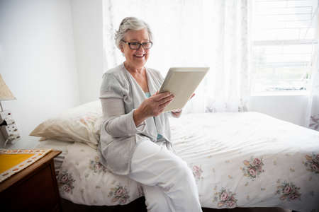 sheltered accommodation: Senior woman looking at her tablet in a retirement home