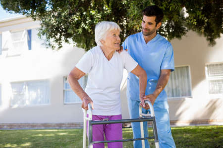 sheltered accommodation: Nurse helping senior woman to walk in a retirement home LANG_EVOIMAGES