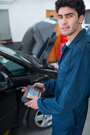 diagnostic tool: Portrait of mechanic using a diagnostic tool at the repair garage