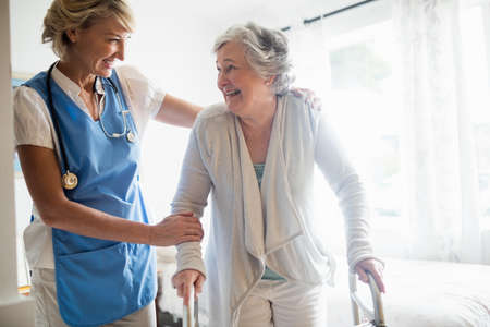 mobility nursing: Nurse helping senior woman to stand up in a retirement home
