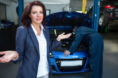 outraged: Worried customer with mechanic examining car at repair garage