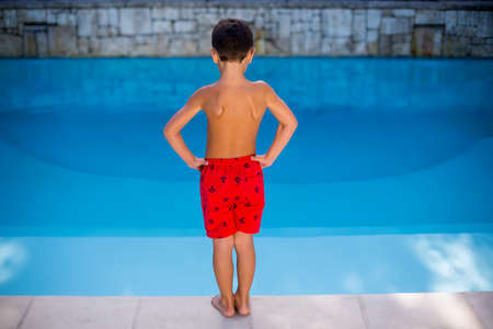 niño sin camisa: Rear view of shirtless boy standing in swimming pool