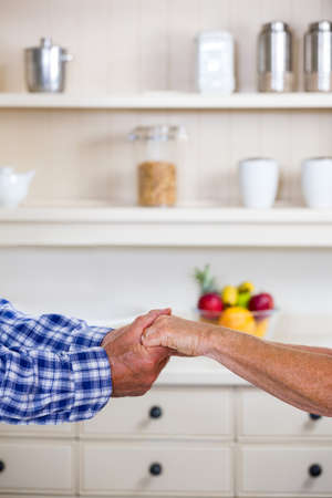 look after: Cropped image of senior couple holding hands in kitchen at home