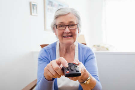 sheltered accommodation: Senior woman holding a remote control in a retirement home LANG_EVOIMAGES
