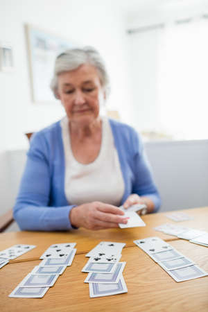 sheltered accommodation: Senior woman playing cards in a retirement home