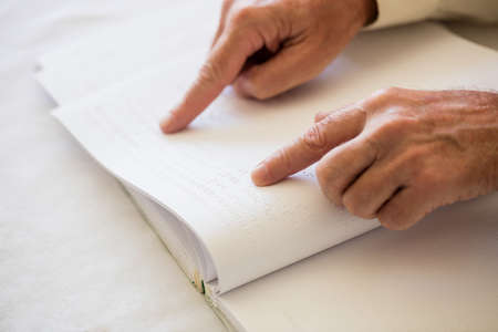 sheltered accommodation: Blind senior woman using braille to read in a retirement home