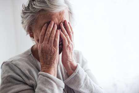 sheltered accommodation: Senior woman hiding her face with her hands in a retirement home