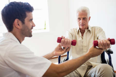 sheltered accommodation: Nurse helping senior man with doing exercises in a retirement home LANG_EVOIMAGES