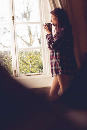looking through window: Young woman holding a coffee mug looking through window