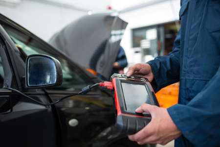 diagnostic tool: Mid section of mechanic using a diagnostic tool at the repair garage