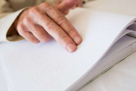 braile: Mujer mayor que usa braille para leer en una casa de retiro