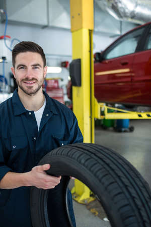 shop skill: Portrait of mechanic holding a tyre at the repair garage