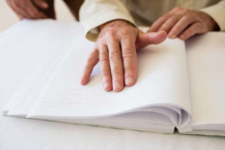 braille: Senior woman using braille to read in a retirement home LANG_EVOIMAGES