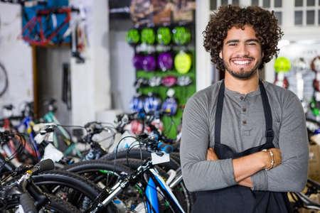 crossing arms: Cheerful bike dealer crossing arms in bikeshop