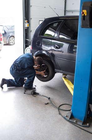 pneumatic: Mechanic changing car wheel with pneumatic wrench at the repair garage