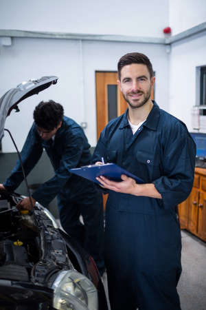 engine bonnet: Mechanic preparing a check list while his colleague examining a car engine in the background