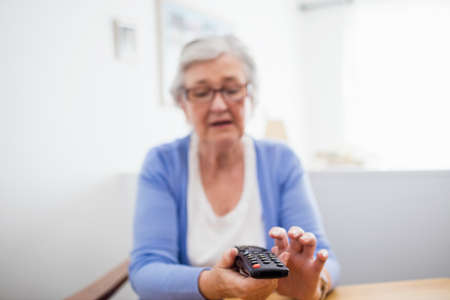 changing channel: Senior woman holding a remote control in a retirement home LANG_EVOIMAGES