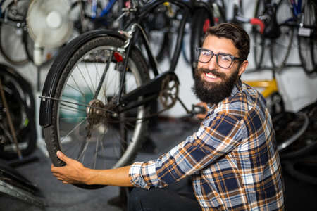 verifying: Bike mechanic checking at bicycle in bike repair shop