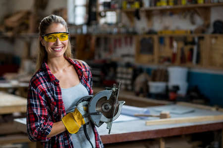 circular saw: Portrait of female carpenter standing with circular saw in workshop