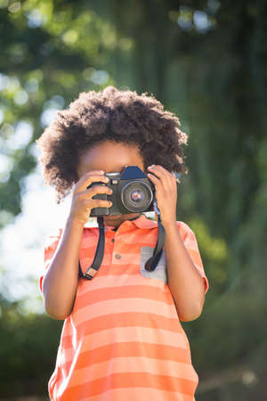 looking through an object: Boy is taking pictures in a park LANG_EVOIMAGES