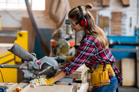 electric saw: Female carpenter cutting wooden plank with electric saw in workshop