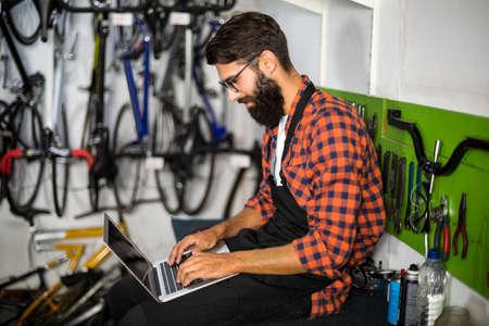 repair shop: Bike mechanic checking laptop in bike repair shop
