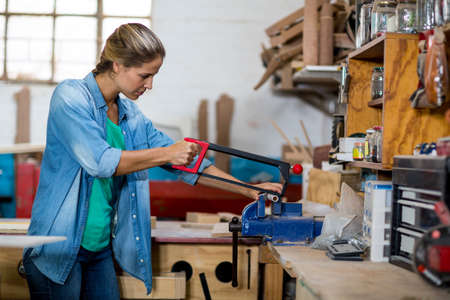 coping: Female carpenter using coping saw to cut the piece of wood in workshop
