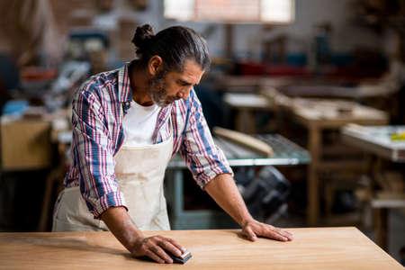 sanding block: Carpenter rubbing wood with sanding block in workshop