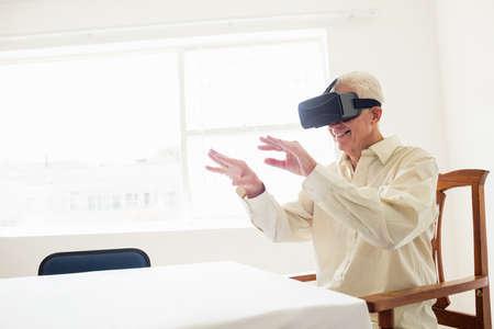 rift: Senior man using an oculus rift in a retirement home