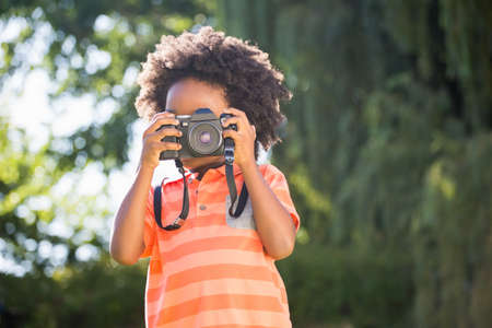 peacefull: Boy is taking pictures in a park LANG_EVOIMAGES
