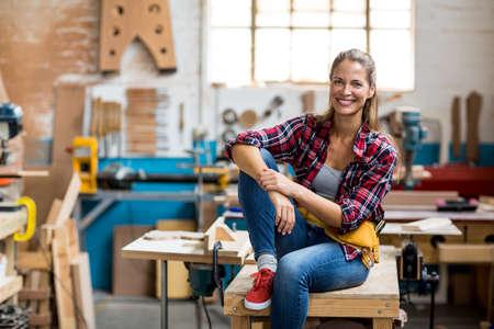 carpenter's bench: Portrait of female carpenter sitting on table in workshop