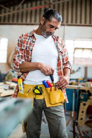 tool belt: Carpenter removing chisel from tool belt in workshop
