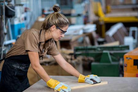 rubbing: Female carpenter rubbing wood with sanding block in workshop