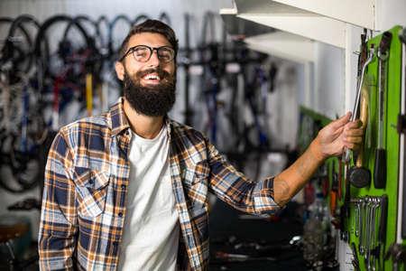 repair shop: Bike mechanic picking up a tool in bike repair shop LANG_EVOIMAGES