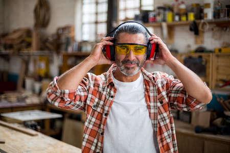 muff: Portrait of carpenter holding ear muff in workshop LANG_EVOIMAGES