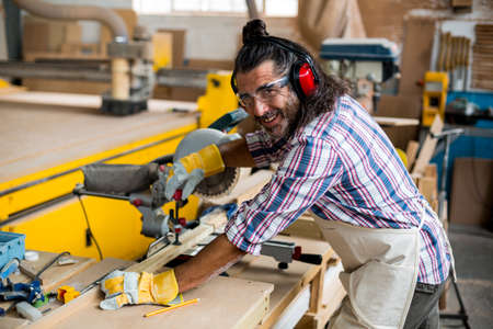 electric saw: Portrait of carpenter cutting wooden plank with electric saw in workshop