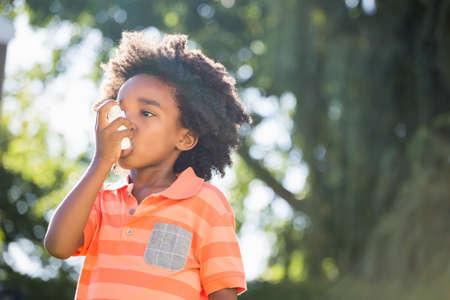 asthmatic: Cute mixed-race boy using a asthmatic spray on a park