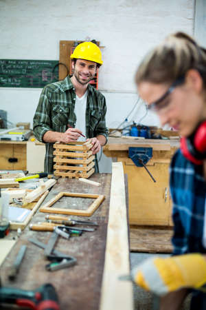 muff: Male and female carpenters working together in workshop LANG_EVOIMAGES
