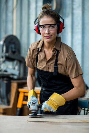 muff: Female carpenter polishing a wooden plank with polishing machine in workshop