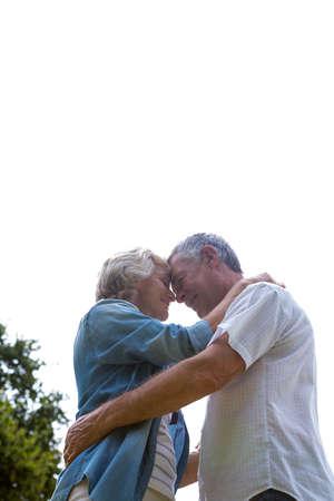 back yard: Loving senior couple embracing in back yard against clear sky
