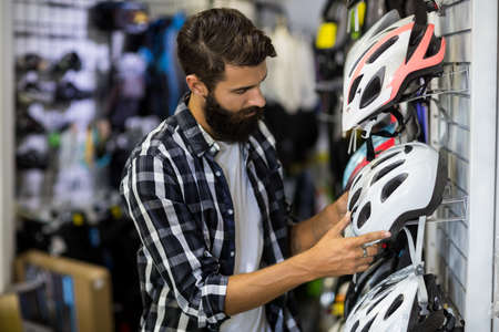 repair shop: Hipster customer picking up a helmet in bike repair shop LANG_EVOIMAGES
