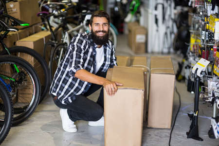 repair shop: Casual hipster picking up box delivery in bike repair shop LANG_EVOIMAGES