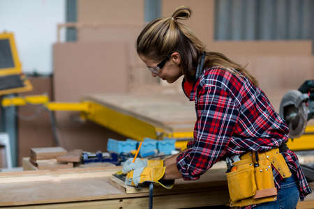 carpenter's bench: Female carpenter marking on wooden plank with pencil in workshop